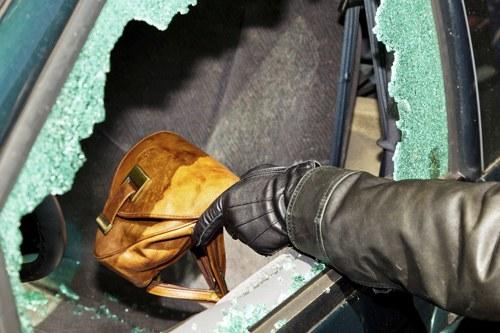 Eine Hand greift durch ein eingeschlagenes Autofenster ins Innere des Fahrzeuges.